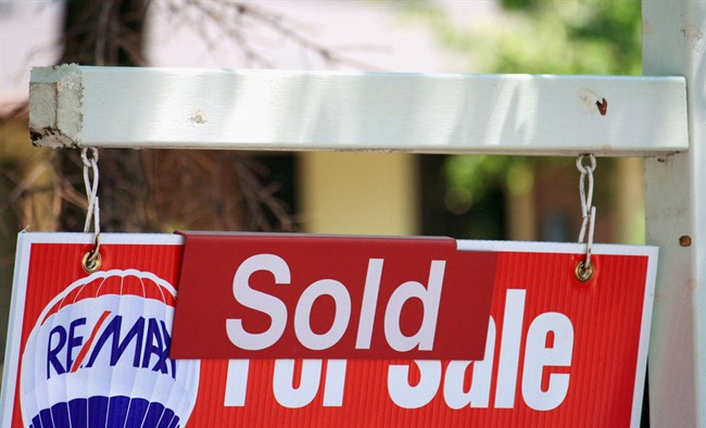 """A house """"sold"""" sign in Oakville, Ont., on July 23, 2012."""