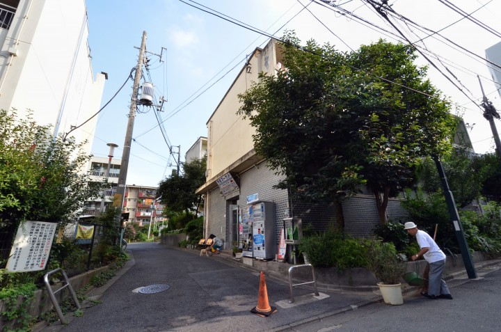 In this picture taken on September 14, 2013, 79-year-old resident Kohei Jinno (R) sweeps and cleans a road before his apartment complex near the rebuilt national stadium in Tokyo.