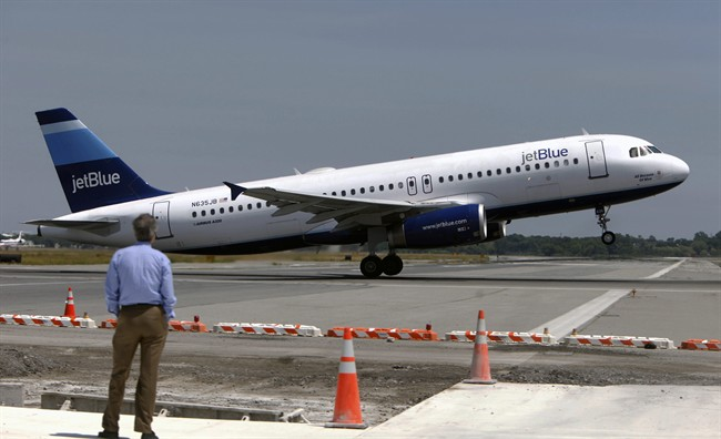 In this Wednesday, June 2, 2010, file photo, a man watches a JetBlue airplane take off from John F. Kennedy International Airport in New York.