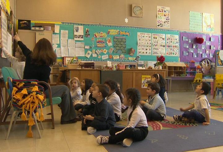 School children sit in a classroom.