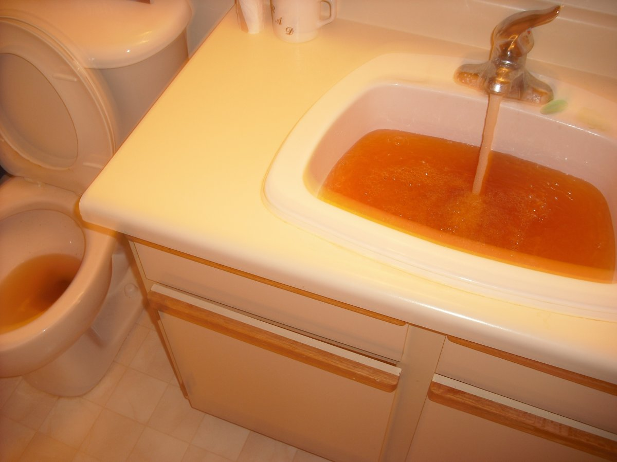 Brown water pours from a tap in Winnipeg in fall.