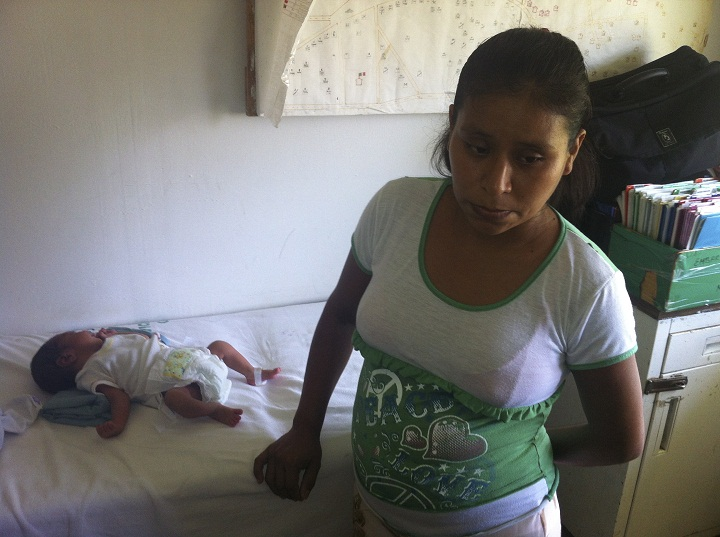 """In this Oct. 6, 2013 photo, 29-year-old Irma Lopez stands next to her newborn son Salvador at a clinic in the town of Jalapa de Diaz, Mexico. Mexico officials have suspended a health center director after Lopez, an indigenous woman, was denied entry to his clinic and was forced to give birth on the lawn. A nurse kicked Lopez out of the clinic Oct. 2, claiming she was """"still not ready"""" and had to wait for a doctor. After an hour and half, Lopez gave birth while grabbing the wall of a house next to the clinic."""