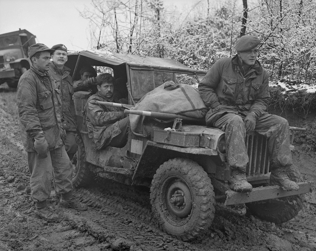 The morning after an artillery attack in Korea in November of 1951. Canadian troops wait to take a soldier's body away for burial.