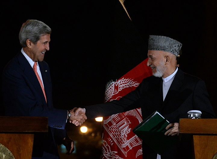 Afghanistan's president Hamid Karzai (R) shakes hand with US Secretary of State John Kerry during a joint press conference at the presidential palace in Kabul on October 12, 2013. US Secretary of State John Kerry said a long-delayed deal on the future of US forces in Afghanistan could not be signed unless the issue of immunity for troops was solved. 'We need to say that if the issue of jurisdiction can not be resolved, unfortunately there can not be a bilateral security agreement', he said.