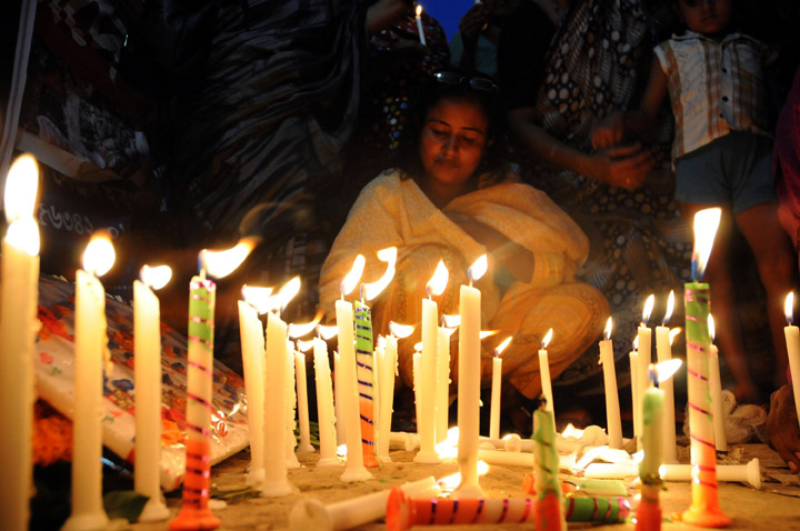 Bangladeshi garment workers and relatives of victims of the Rana Plaza building collapse hold candles during a memorial at the site of the Rana Plaza garment factory building collapse in Savar, on the outskirts of Dhaka on October 24, 2013, the six-month anniversary of the disaster.