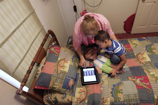 Denise Thevenot and her son Frankie Thevenot, 3, play with an iPad in his bedroom at their home in Metairie, La., on Oct. 21, 2011.