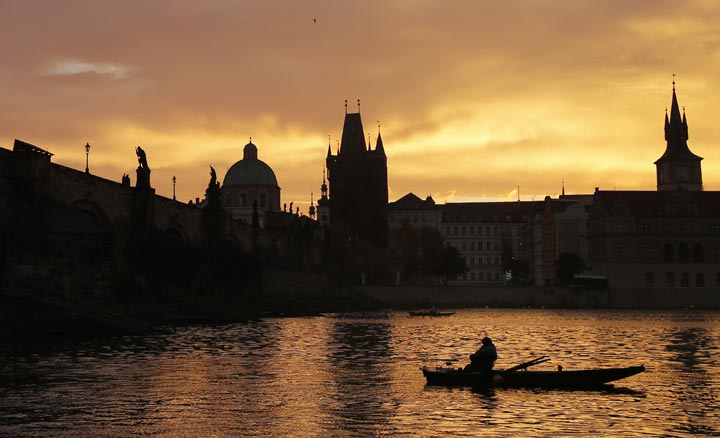 A fisherman waits for a catch underneath the medieval Charles Bridge as the sun rises in Prague, Czech Republic, Thursday, Oct. 17, 2013.  AP Photo/Petr David Josek.