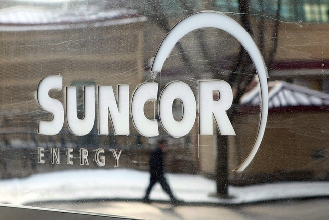 A pedestrian is reflected in a Suncor Energy sign in Calgary, Feb. 1, 2010.