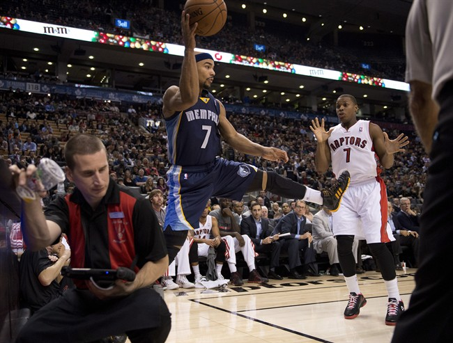 Memphis Grizzlies Jerryd Bayless (left) flies out of bounds as he saves a ball past Toronto Raptors Kyle Lowry (right) during first half pre-season NBA action in Toronto on Wednesday October 23, 2013.