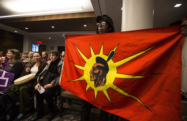 An indigenous man holds a flag during the National Energy Board public hearings on Enbridge Line 9 oil pipeline, in Toronto, Friday October 18, 2013.