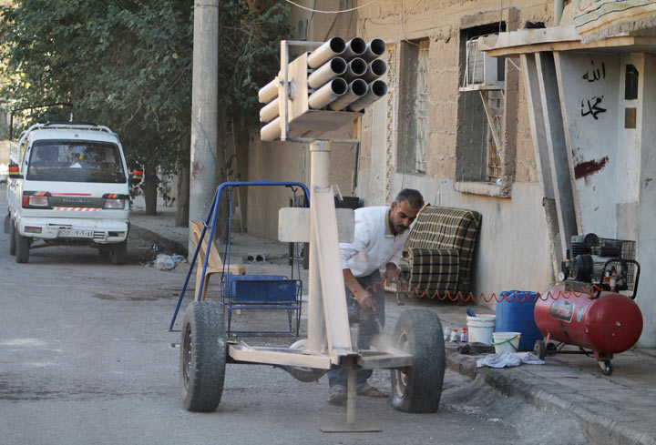 A man paints a homemade multi-rocket launcher in the Jubaila neighbourhood of Syria's northeastern city of Deir Ezzor on October 11, 2013.