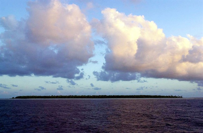 In this Dec. 30, 1999 file photo, clouds float over the Millennium Island, Kiribati, in the South Pacific.
