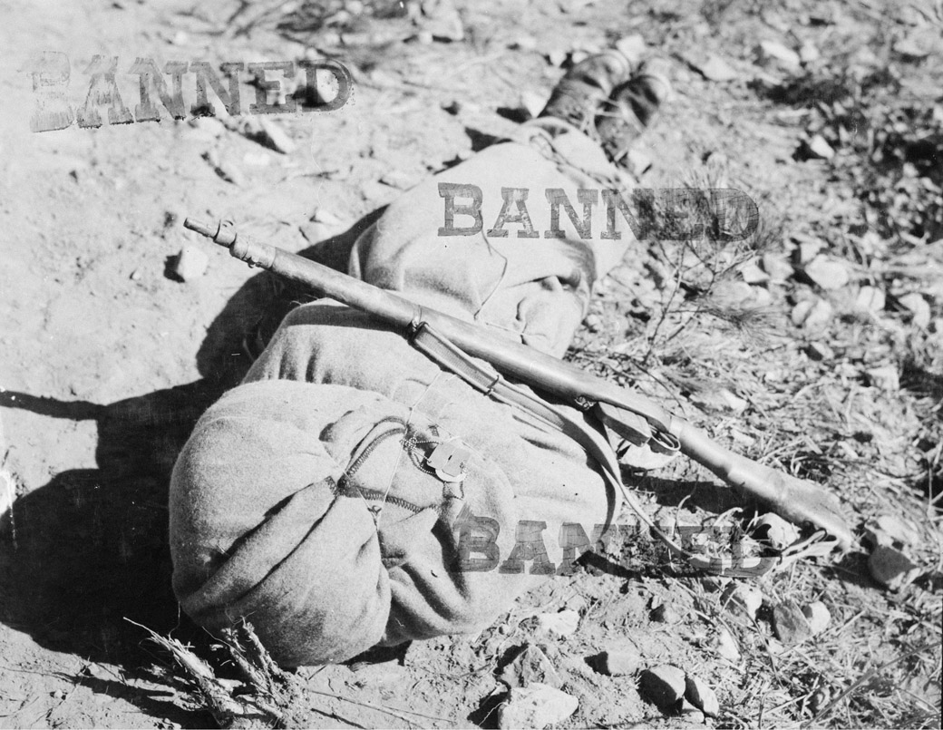 The body of a Canadian infantryman awaits burial in Korea, November, 1951. His identity tag and what appear to be religious medals with text in French are attached to the blanket. A battlefield censor forbade publication of the image.