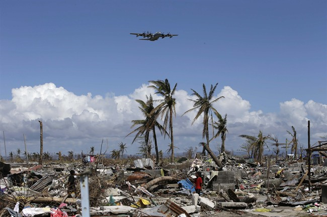 A US Navy C-130 cargo plane carrying typhoon survivors, flies over the devastation, as others sift through the debris in Tacloban city Monday Nov. 25, 2013 in Leyte province in central Philippines. THE CANADIAN PRESS/AP, Bullit Marquez.