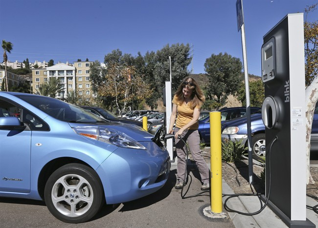 Angie Vorhies plugs in the charging cord to her Nissan Leaf electric vehicle at a mall Wednesday, Nov. 13, 2013, in San Diego.
