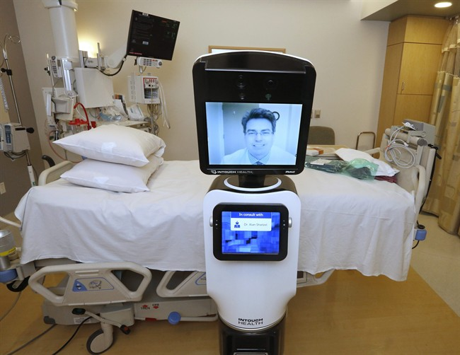 """In this photo taken Wednesday, Nov. 6, 2013, Dr. Alan Shatzel, medical director of the Mercy Telehealth Network, is displayed on the monitor RP-VITA robot at Mercy San Juan Hospital in Carmichael, Calif. The robots enable physicians to have a different bedside presence as they """"beam"""" themselves into hospitals to diagnose patients and offer medical advice during emergencies. (AP Photo/Rich Pedroncelli)."""