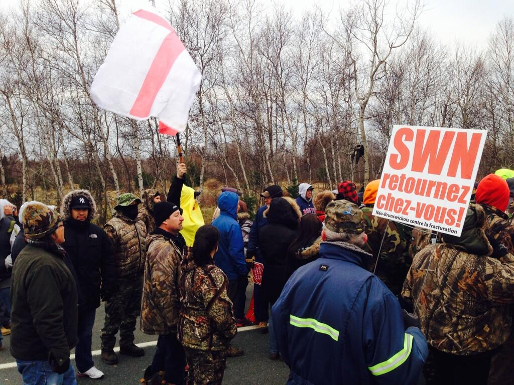 Protesters cheer after trucks owned by SWN Resources leave the scene of shale gas protests near Laketon, N.B. on Nov. 14, 2013.
