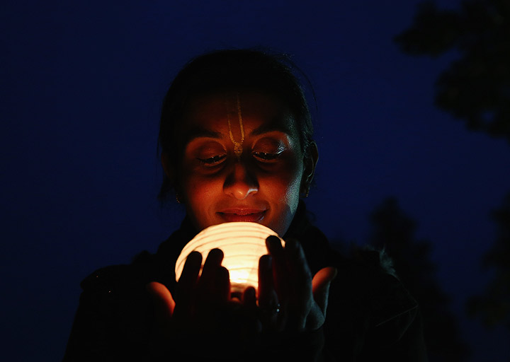 A woman holds a lantern during Diwali celebrations at Bhaktivedanta Manor on November 3, 2013 in Watford, United Kingdom. The festival is an opportunity for Hindus to honour Lakshmi, the goddess of wealth and other gods. Leicester's celebrations are one of the biggest in the world outside India. (Photo credit: Getty Images).