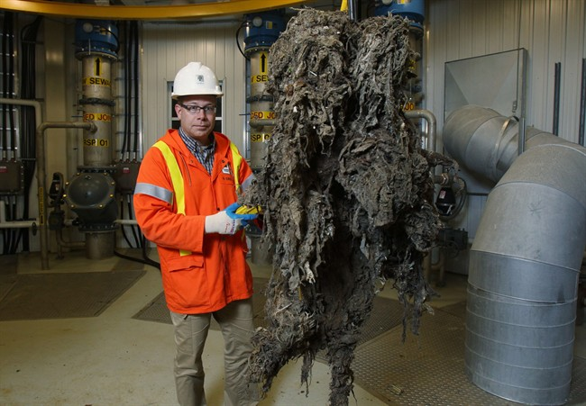 Barry Orr of the City of London Environmental and Engineering Services lifts a giant mass of material, primarily wipes that are supposed to be flushable, that had been clogging the sewage system pumps in London, ON, Friday, Nov. 15, 2013.