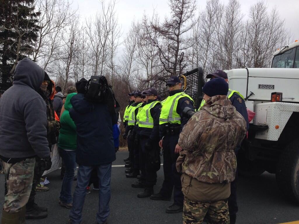 RCMP officers form a line between protesters and SWN Resources seismic testing trucks near Laketon, N.B. on Nov. 14, 2013.