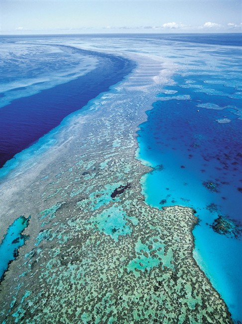 In this Sept. 2001 file photo provided by provided by Queensland Tourism, an aerial view shows the Great Barrier Reef off Australia's Queensland state. Starvation, poverty, flooding, heat waves, droughts, war and disease already lead to human tragedies. They're likely to worsen as the world warms from man-made climate change, a leaked draft of an international scientific report forecasts. Australia and New Zealand get the unique risk of losing their coral reef ecosystems, and small island nations have to be worried about being inundated by rising seas. (AP Photo/Queensland Tourism, File) .