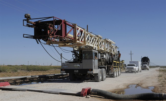 A drilling rig used for hydraulic fracturing is trucked across a water hose at a drill site Sept. 24, 2013, in Midland, Texas.