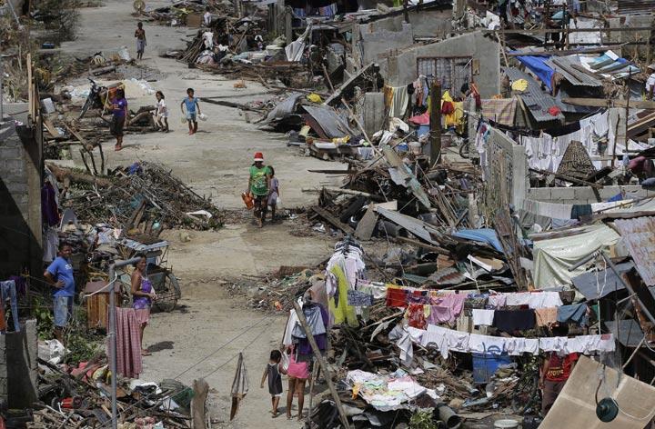 Survivors of Typhoon Haiyan walk amid ruins of their homes in Maraboth, Philippines, Thursday, Nov. 14, 2013.