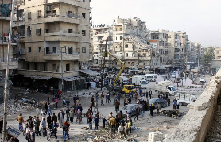 Syrians look at the aftermath of airstrikes by government forces on the northern Syrian city of Aleppo on November 24, 2013.