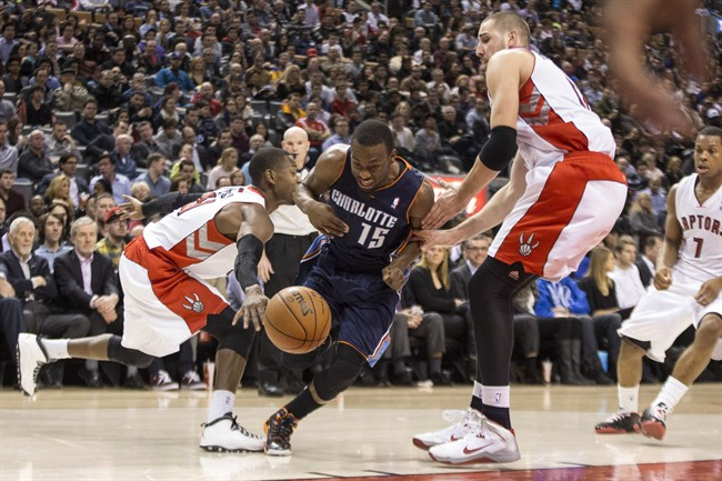 Charlotte Bobcats' Kemba Walker (centre) drives between Toronto Raptors' Jonas Valanciunas (right) and Terrence Ross during first half NBA basketball action in Toronto on Wednesday December 18 , 2013.