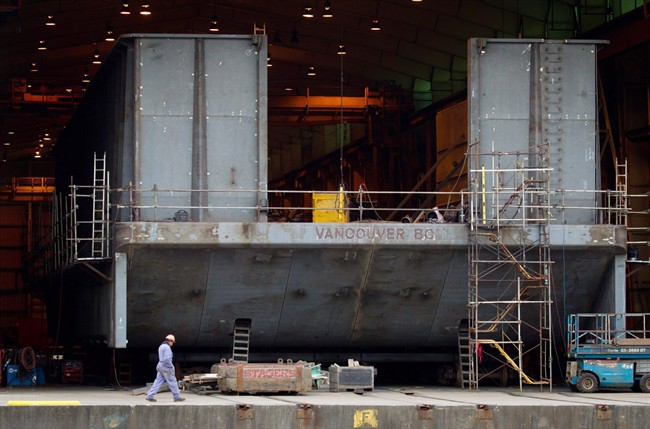 File photo - A Seaspan Vancouver Shipyards worker walks past a barge under construction on Wednesday November 2, 2011.