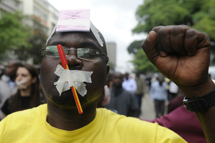 A man with tape on his face take part in a march called by Kenyan journalists on december 3, 2013 in Nairobi, to protest a bill voted par the parliament last month to set up a special quasi-government body to police the media, with the power to slap huge fines on journalists and outlets if they violate a code of conduct.