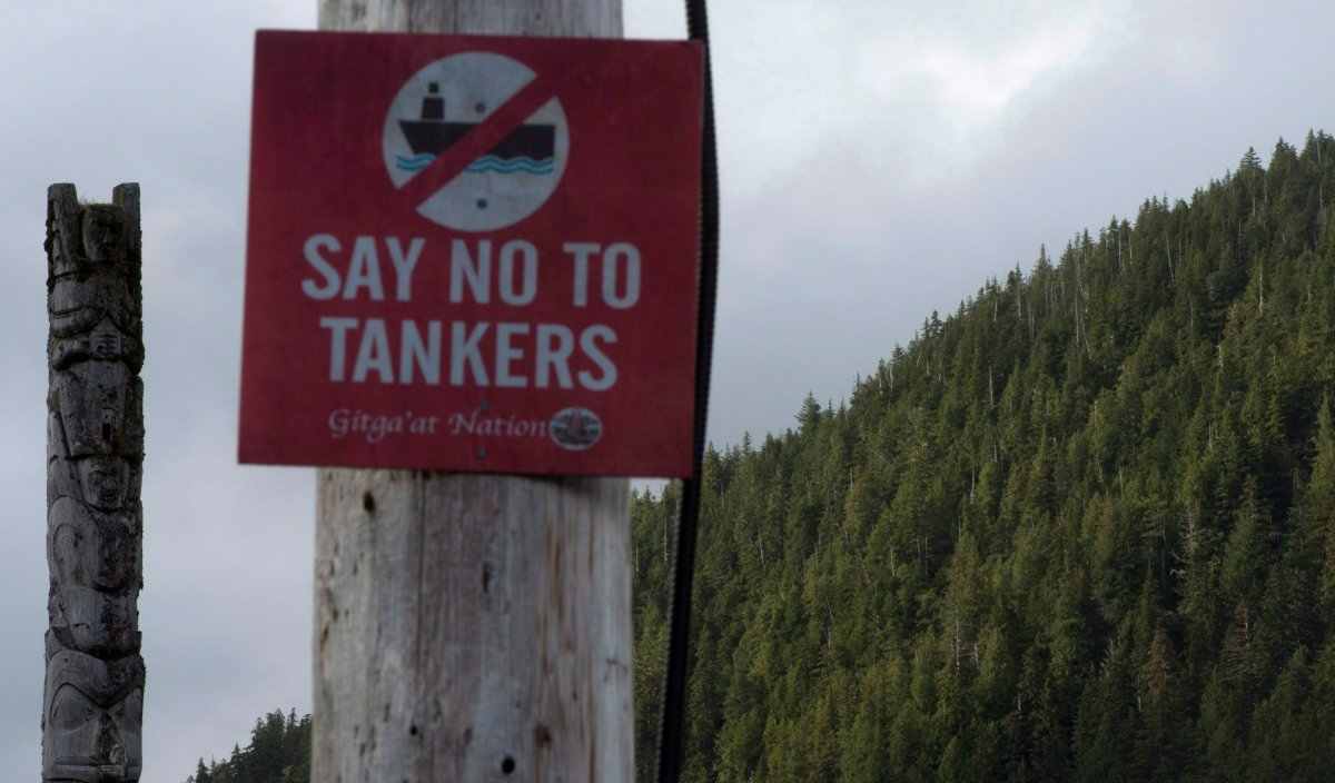An anti-tanker sign is seen with an ancient totem pole in the background in Hartley Bay, B.C. Tuesday, Sept, 17, 2013.