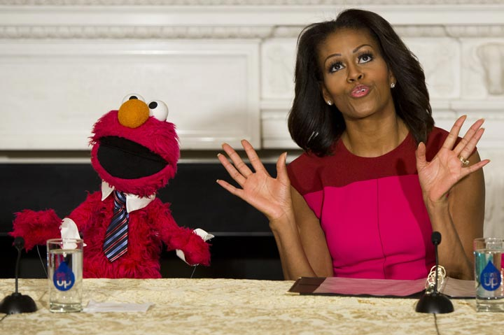 U.S. First Lady Michelle Obama dances alongside Sesame Street character Elmo.