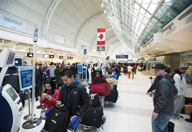 Passengers line-up during flight delays at Pearson International Airport in Toronto on Tuesday January 7, 2014. THE CANADIAN PRESS/Aaron Vincent Elkaim