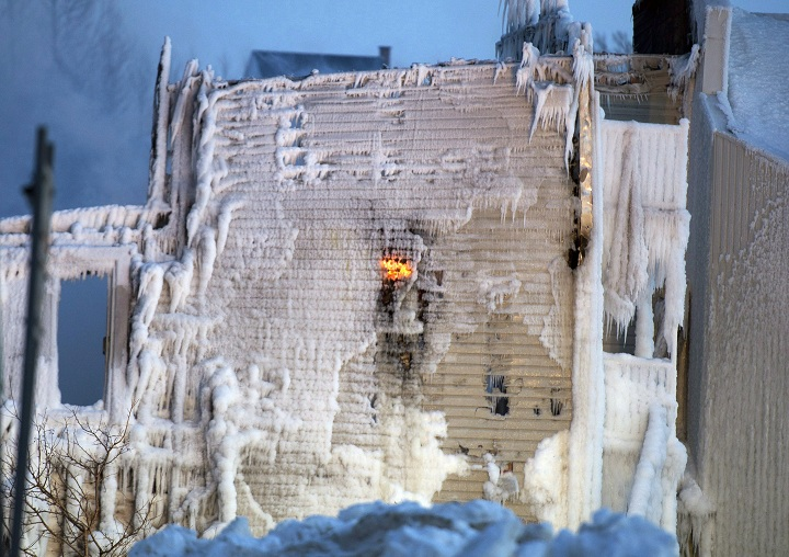Flames flare up through a wall at the scene of a fatal fire which destroyed a seniors residence in L'Isle-Verte, Que., Thursday, January 23, 2014.