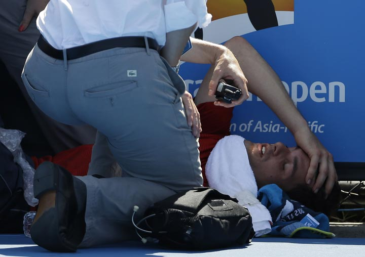 Frank Dancevic of Canada lies on the court after collapsing during his first round match against Benoit Paire of France as temperatures topped at 43 C (108 F) at the Australian Open tennis championship in Melbourne, Australia, Tuesday, Jan. 14, 2014.