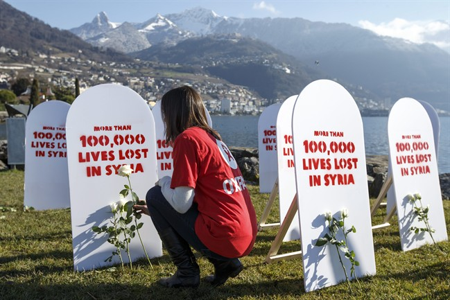 """A member of movement Oxford Committee for Famine Relief, """"Oxfam"""", puts a white rose on symbolic gravestones, on the opening day of the Geneva II peace talks on Syria, in Montreux, Switzerland, Wednesday, Jan. 22, 2014."""