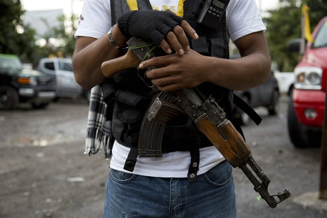 In this Jan. 16, 2014 file photo, an armed man belonging to the Self-Defense Council of Michoacan, (CAM), stands guard at a checkpoint set up by the self-defense group at the entrance to Antunez, Mexico.