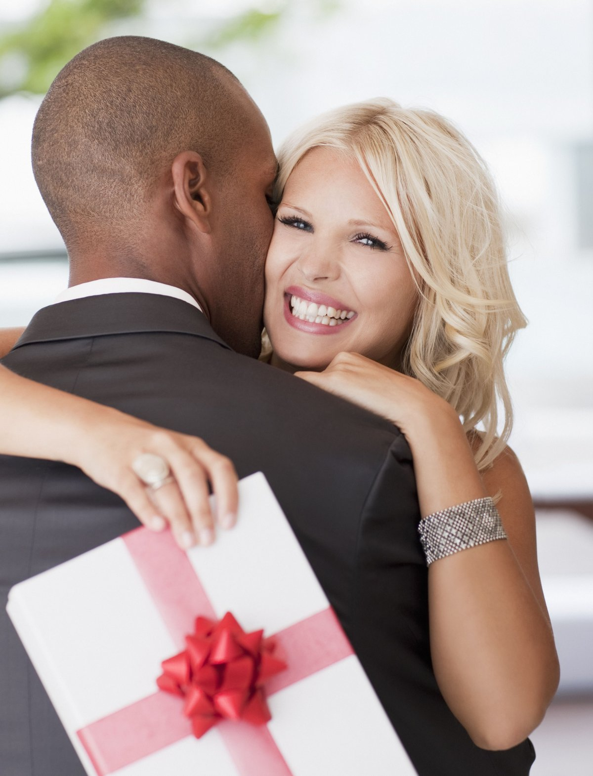 Stock photo: Woman with gift hugging man
