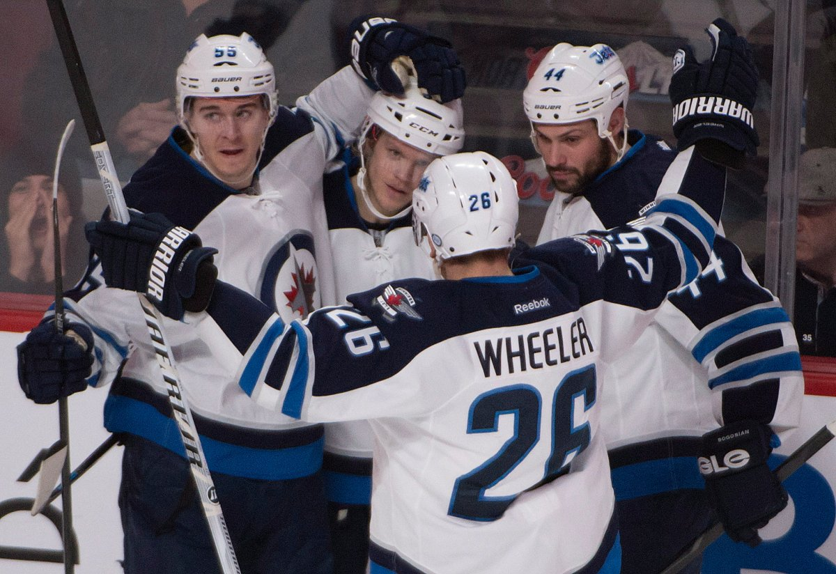 Winnipeg Jets' Tobias Enstrom, second from left, gets congratulated by teammates Mark Scheifele (55), Blake Wheeler (26) and Zach Bogosian (44)after scoring against the Montreal Canadiens during second period NHL action in Montreal on Sunday, February 2, 2014.