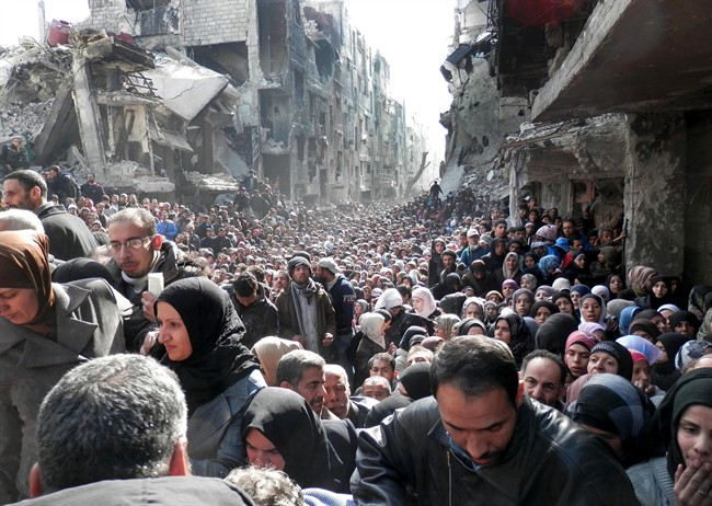 This picture taken on Jan. 31, 2014, and released by the United Nations Relief and Works Agency for Palestine Refugees in the Near East (UNRWA), shows residents of the besieged Palestinian camp of Yarmouk, queuing to receive food supplies, in Damascus, Syria.
