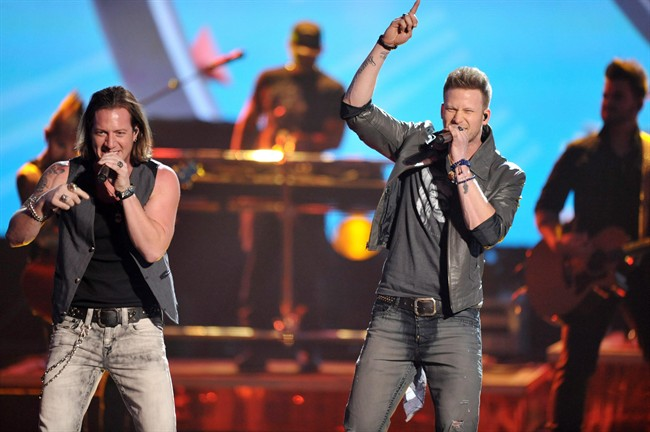 """Tyler Hubbard, left, and Brian Kelley of the musical group Florida-Georgia Line perform on stage at the American Music Awards at the Nokia Theatre L.A. Live on Sunday, Nov. 24, 2013, in Los Angeles.""""."""
