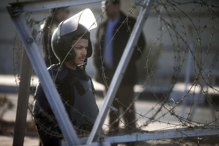 An Egyptian riot policeman stands gard behind barbed wire in front of the main gate of the Police Academy in Cairo on February 5, 2014.