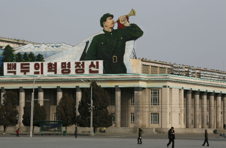 North Korean walk under a sign of a soldier blowing a bugle at Kim Il Sung Square in Pyongyang, North Korea, Tuesday, Feb. 18, 2014.