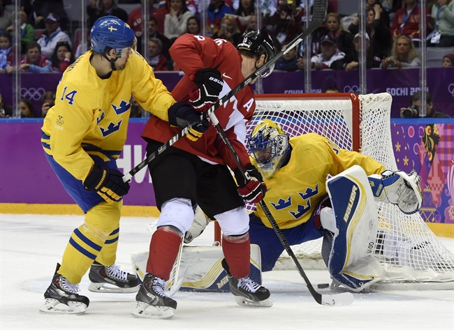 Canada forward Jonathan Toews scores past Sweden goaltender Henrik Lundqvist as Patrik Berglund looks on during first period men's gold medal final hockey action at the Sochi Winter Olympics Sunday, February 23, 2014 in Sochi.