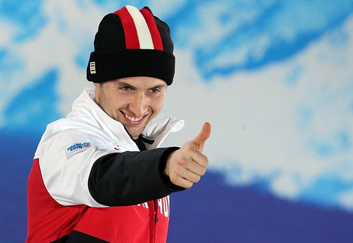 Canada's gold medalist Alex Bilodeau celebrates on the podium during the Men's Freestyle Skiing Moguls Medal Ceremony at the Sochi medals plaza during the Sochi Winter Olympics on February 11, 2014.