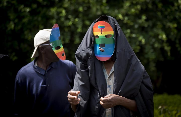 Kenyan gays and lesbians and others supporting their cause wear masks to preserve their anonymity as they stage a rare protest against Uganda's increasingly tough stance against homosexuality and in solidarity with their counterparts there, outside the Uganda High Commission in Nairobi, Kenya Monday, Feb. 10, 2014.
