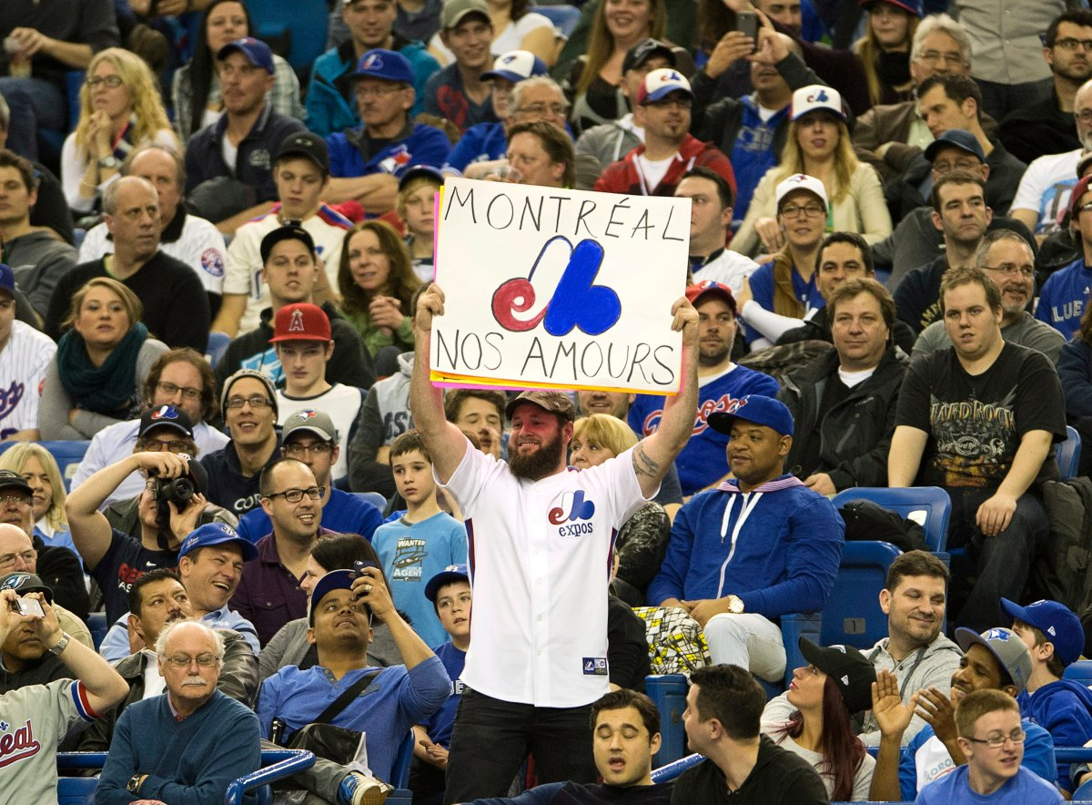 Fans wear Montreal Expos uniforms as they watch the Toronto Blue Jays in a pre-season baseball game against the New York Mets .