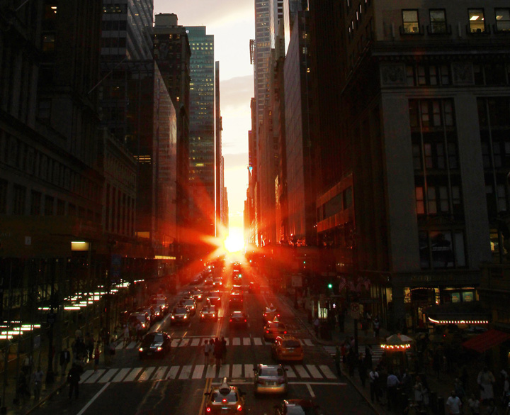 """The sun is seen as it sets between Manhattan buildings on 42nd Street during a phenomenon known as """"Manhattanhenge,"""" , July 13, 2011."""
