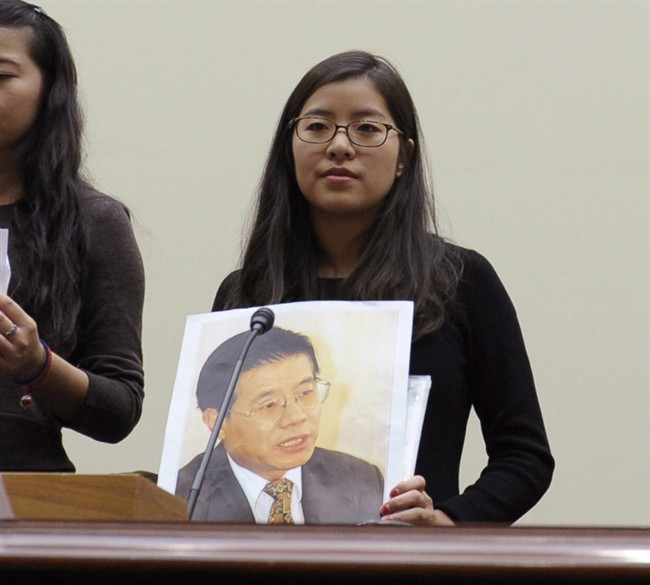 Ti-Anna Wang holds a photo of her father Wang Bingzhang, prior to testifying before the House Foreign Affairs Committee in Washington, Dec. 5, 2013.